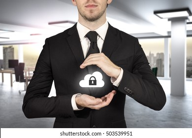 businessman in modern office protect cloud lock symbol with hands