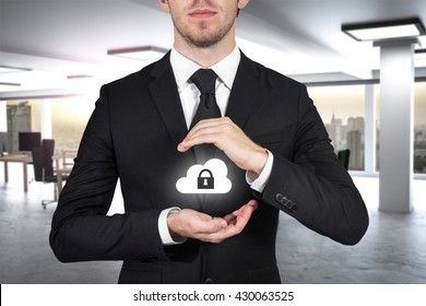 businessman in modern office protecting cloud lock symbol with hands