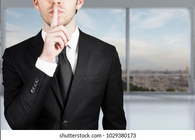 businessman in modern office putting finger on lips sush gesture
