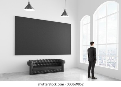 Businessman in modern white light room with chesterfield sofa and blank black poster, mock up 3D Render