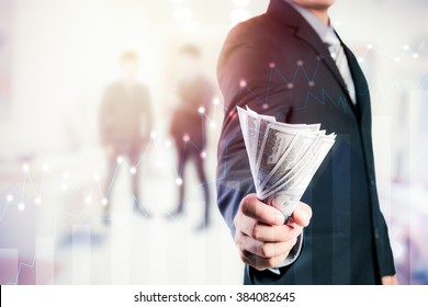 Businessman with money in hand, US dollar (USD) bills - investment, success and profitable business concepts.Forex graph on background. A metaphor of international financial consulting