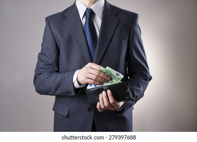Businessman with money in purse in hands on a gray background