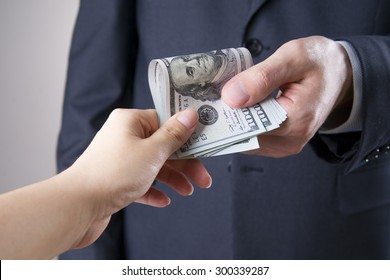 Businessman with money in studio on a gray background. Corruption concept