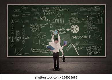 Businessman multitasking with business doodle writings on blackboard