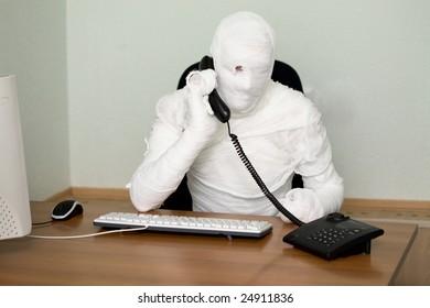 Businessman mummy talking on telephone on white