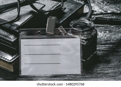 Businessman name badge template. Blank badge, inkwell, quill pen, wallet and book on a black background.