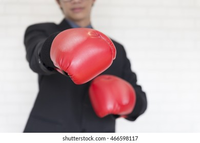 businessman in necktie and suit with red boxing glove punch to you - business competition concept