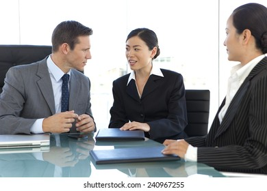Businessman negotiating with Asian businesswoman