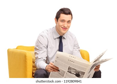Businessman with a newspaper sitting in a yellow armchair isolated on white background