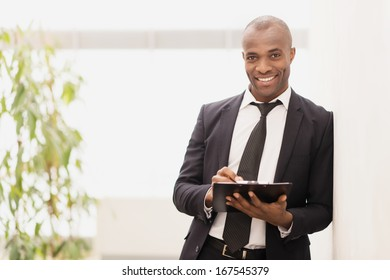 Businessman with note pad. Cheerful young African businessman writing something in his note pad and smiling at camera