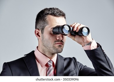 Businessman observing with binoculars isolated over grey