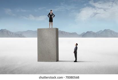 Businessman observing a businesswoman on a high cube