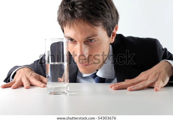 Businessman observing a half full glass of water
