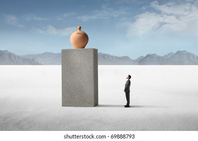 Businessman observing a money box on a high cube