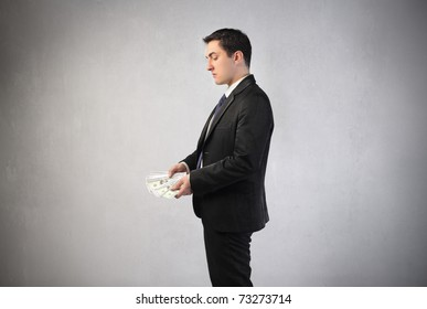 Businessman observing some banknotes in his hands