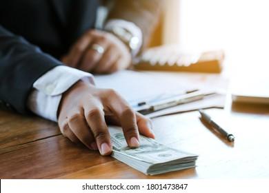 Businessman offering batch of hundred dollar bills. Hands close up. Venality, bribe, corruption concept. Hand receiving money from businessman.