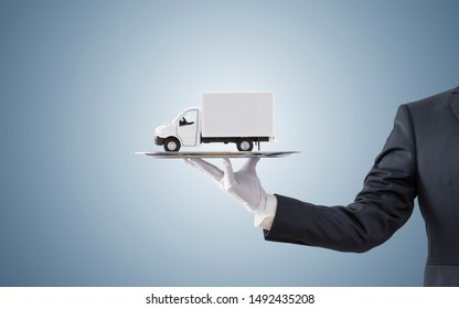 Businessman offering cargo delivery truck on silver tray