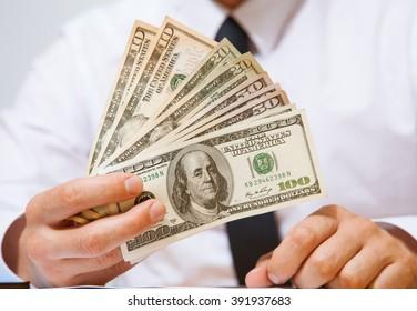 Businessman offering dollars to you - closeup shot