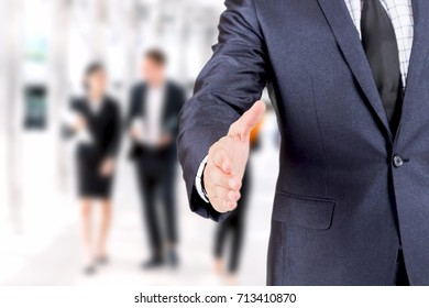 Businessman offering handshake on group of business  background