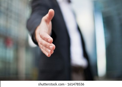 Businessman offering for handshake on office buildings background