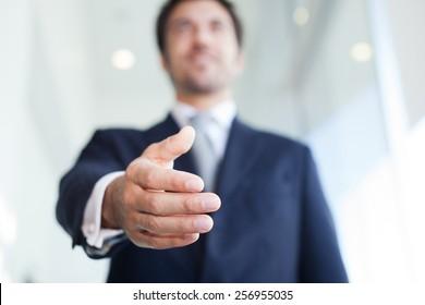 Businessman offering an handshake. Selective focus