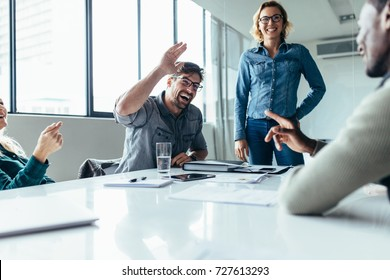 Businessman offering a high five to a coworker during a meeting in conference room. Positive boardroom environment.