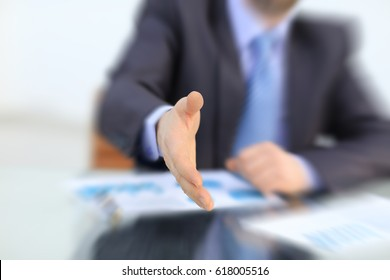 Businessman offering his hand for handshake. Greeting or congratulating gesture.