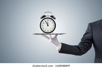 Businessman offering old style alarm clock on silver tray