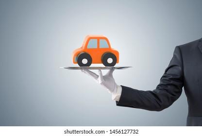 Businessman offering orange car on silver tray
