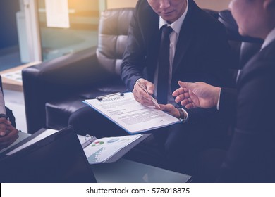 Businessman offering pen to his business partner for sign contract