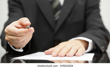 Businessman offering a pen to sign a contract