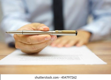 businessman is offering a pen to sign a contract or take a job