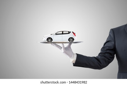 Businessman offering white car on silver tray over gray background