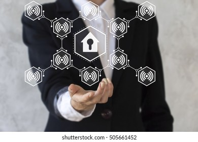 Businessman offers his hand in icon house with keyhole and wireless symbol. Businesswoman offer security home sign in hand. Business success solution sale buy realtor estate. Technology iot wifi.