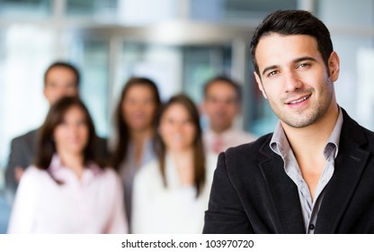 Businessman at the office with a group at the background