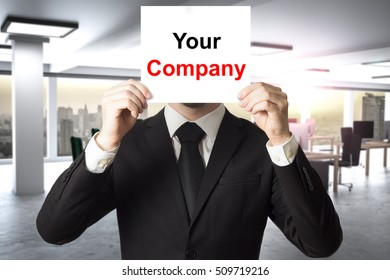 businessman in office hiding face behind sign your company