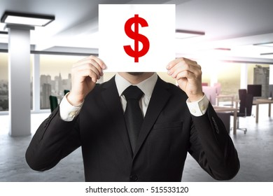 businessman in office hiding face behind sign dollar