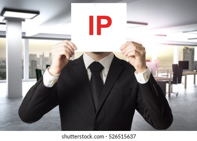 businessman in office hiding face behind sign ip