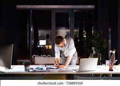 Businessman in the office at night working late.