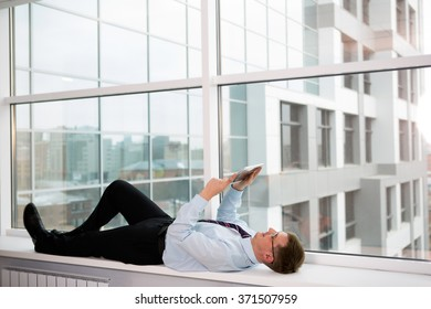 businessman in the office on the background of the windows running on the tablet