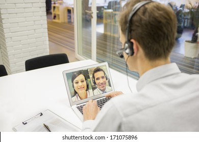 Businessman in the office on video conference, headset, Skype
