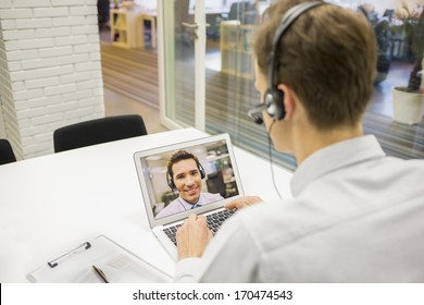 Businessman in the office on videoconference with headset, Skype
