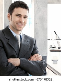 Businessman in office. Portrait of a happy young handsome businessman standing arms crossed, smiling, looking at camera.