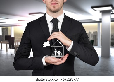 businessman in office protecting papercut family home with hands