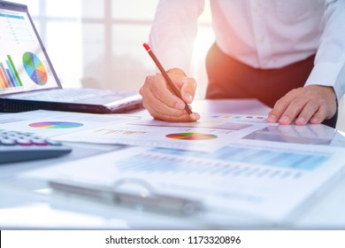 Businessman in the office reviewing financial reports for a return on investment or investment risk analysis in a warm morning light.
