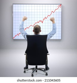 Businessman in office sat on a chair with arms raised in front of a successful growth chart