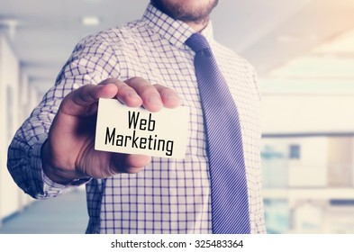 businessman in office showing card with text: Web Marketing
