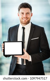 Businessman in the office showing digital tablet with blank screen