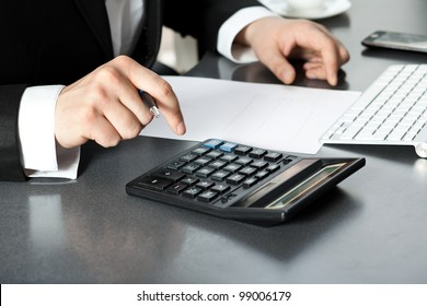 Businessman in office sitting by computer and finds the calculator