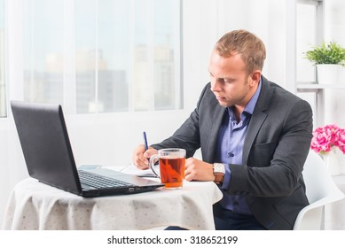 Businessman in office sitting at table with a laptop writes concentration